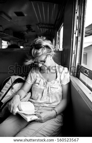 Woman reading book on a train - stock photo