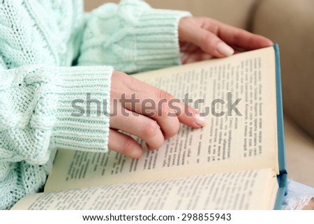 Woman reading book on sofa close up - stock photo