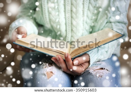 Woman reading book on sofa over snow effect - stock photo