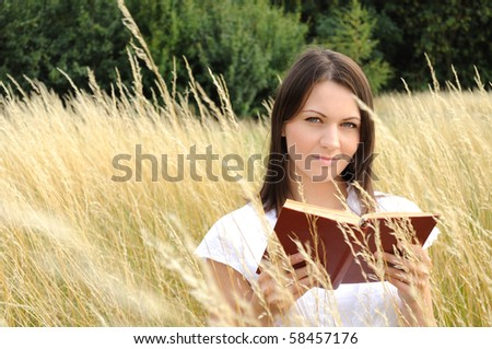 Woman reading book outdoor - stock photo