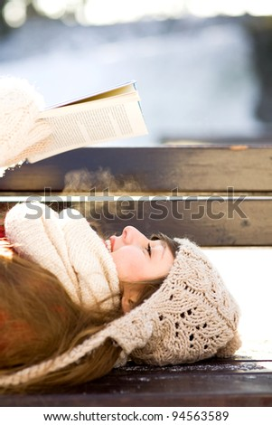 Woman reading book outdoors at winter time - stock photo