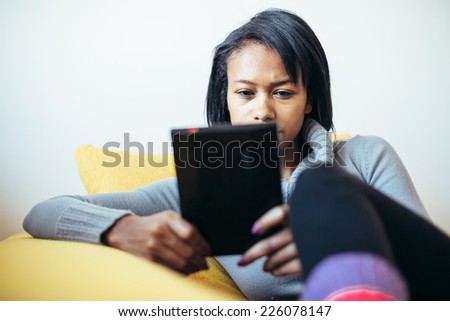 Woman reading ebook on the couch - stock photo