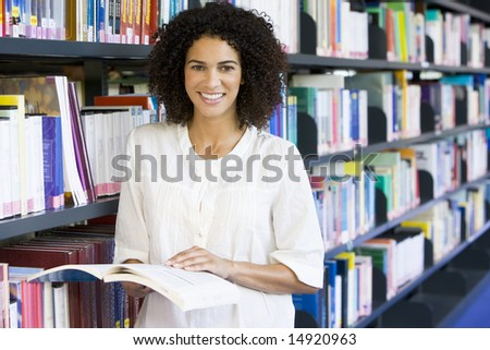 Woman reading in a library - stock photo