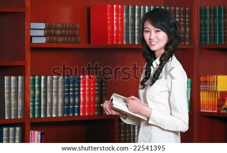 Woman reading in library - stock photo