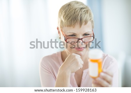 Woman reading instructions on pill bottle - stock photo