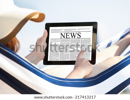 Woman reading newspaper on digital tablet while relaxing in hammock at beach - stock photo