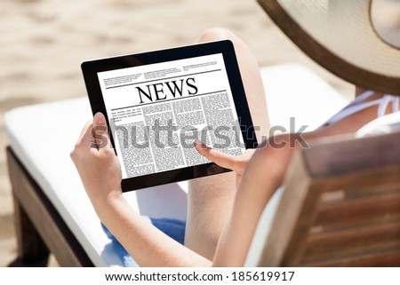 Woman reading newspaper on digital tablet while relaxing on deck chair at beach - stock photo
