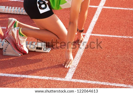Woman ready to start running on running track. - stock photo
