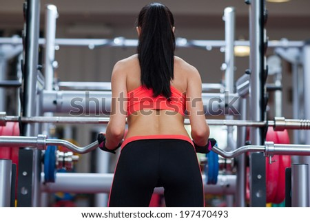 Woman rear view back buttocks in gym sport exercising with barbell lifting weights, young girl working out - stock photo