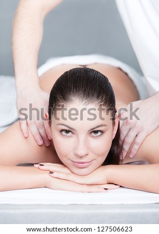 Woman receives shoulders massage at spa salon - stock photo