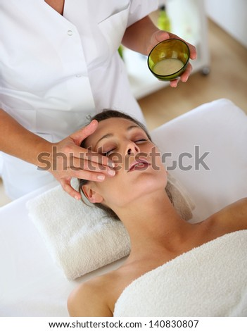 Woman receiving a face massage - stock photo