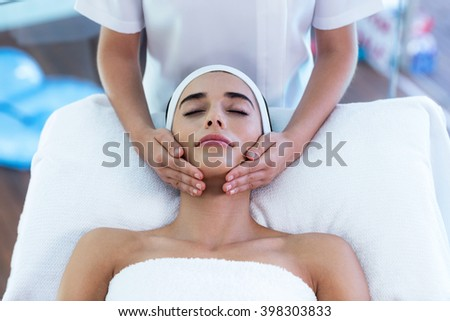 Woman receiving a face massage at spa - stock photo
