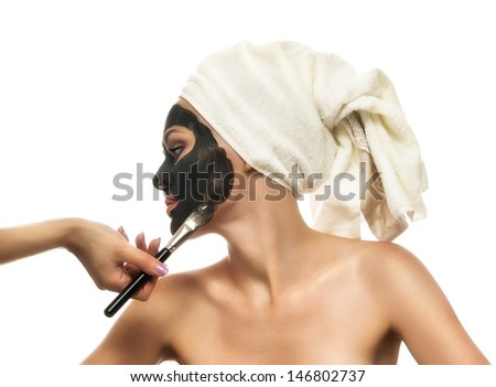 Woman receiving a mud mask. Eyes shut, looking relaxed.Skin Care in beauty salon - stock photo