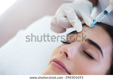 Woman receiving botox injection at spa - stock photo