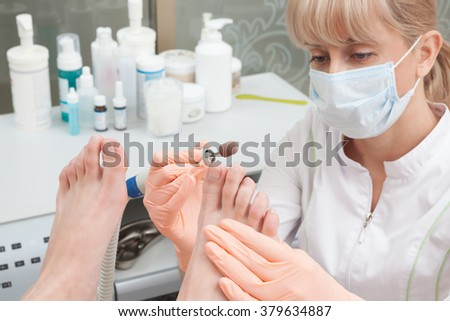 Woman receiving pedicure in a Day Spa, feet nails get cut and filed - stock photo
