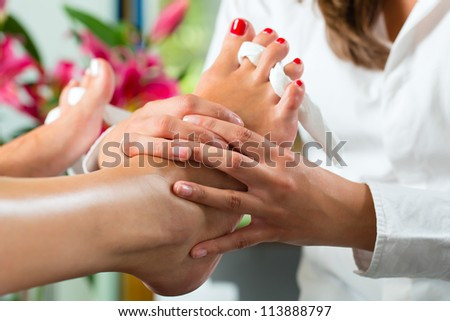 Woman receiving pedicure in a Day Spa, feet nails get polished and she is getting a foot massage - stock photo
