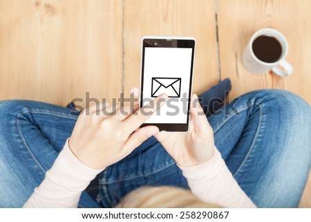 woman receiving/sending a message on smartphone - stock photo