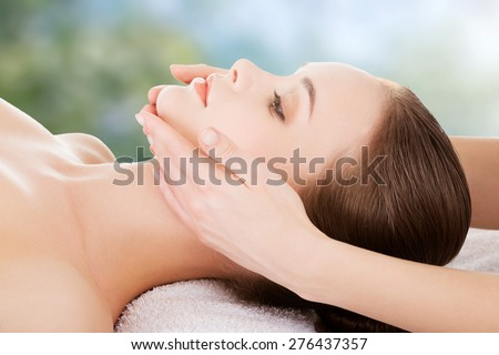 Woman receving face massage in spa. - stock photo