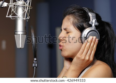 Woman recording a song in a music studio - stock photo