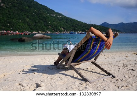woman relax on beach chairs among tropical white sand beach - stock photo