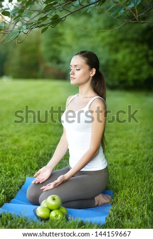 woman relaxation on green grass with apples. Outdoors - stock photo