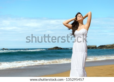 Woman relaxing and enjoying summer vacation on beach. Happy caucasian girl in Playa de Verdicio, Asturias, Spain. Copy space. - stock photo
