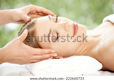 Woman relaxing at a spa having a facial treatment lying back with her eyes closed in enjoyment and a serene expression in a beauty and wellness concept - stock photo