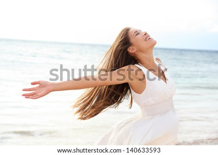 Woman relaxing at beach enjoying summer freedom with open arms and hair in the wind by the water seaside. Mixed race Asian Caucasian girl on summer travel holidays vacation outside. - stock photo
