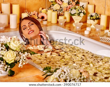 Woman relaxing at flower water spa. Luxury bathroom in spa salon. - stock photo