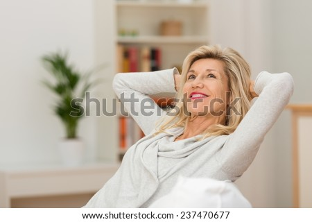 Woman relaxing at home with a contented smile as she leans back in her chair with her hands behind her head looking up into the air with a look of pleasure - stock photo