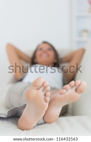 Woman relaxing at home with her feet up on the sofa - stock photo