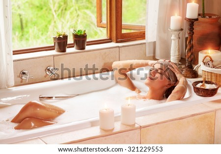 Woman relaxing at spa resort, lying down in the bath with closed eyes and make a compress, pleasure and healthy lifestyle 