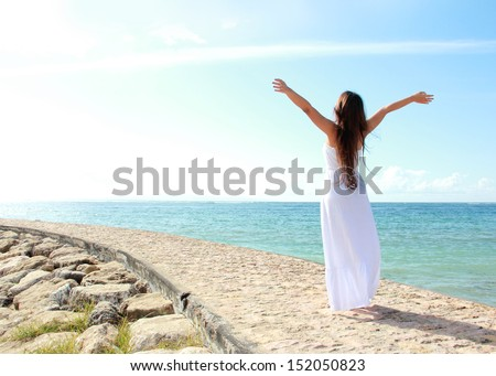 Woman relaxing at the beach with arms open enjoying her freedom wear long white dress - stock photo