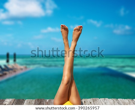 Woman relaxing at the pool - stock photo