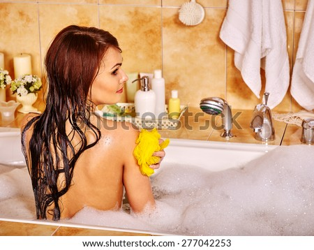 Woman relaxing at water in bubble bath. Washcloth washing shoulder - stock photo