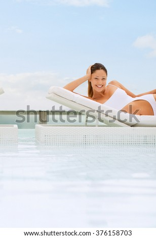 woman relaxing by the swimming pool - stock photo