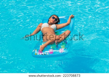 Woman relaxing in a swimming pool - stock photo