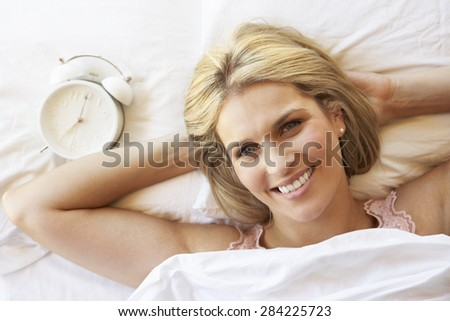 Woman Relaxing In Bed With Alarm Clock - stock photo