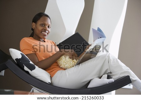 Woman relaxing in curved chair at home, reading magazine, feet up, smiling, side view, portrait (tilt) - stock photo