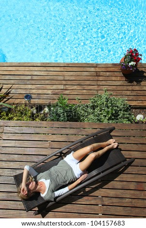 Woman relaxing in deck chair by swimming pool - stock photo