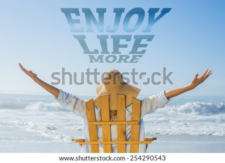 Woman relaxing in deck chair by the sea against enjoy life more - stock photo
