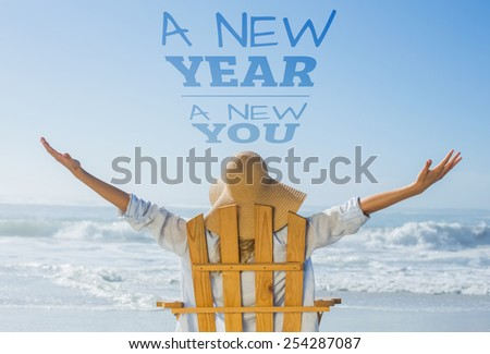 Woman relaxing in deck chair by the sea against new year new you - stock photo
