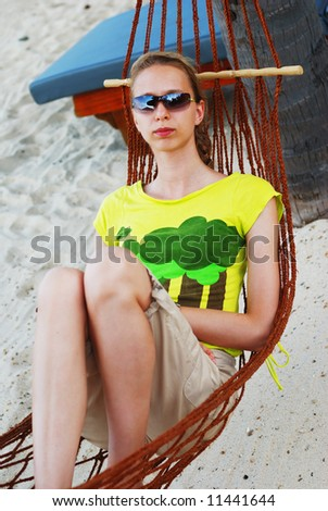 Woman relaxing in hammock on the tropical beach. Sky & palms reflection in sunglasses. - stock photo