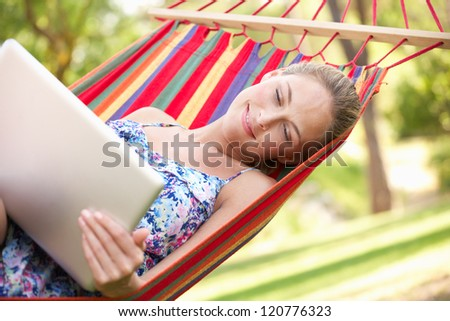 Woman Relaxing In Hammock With Laptop - stock photo