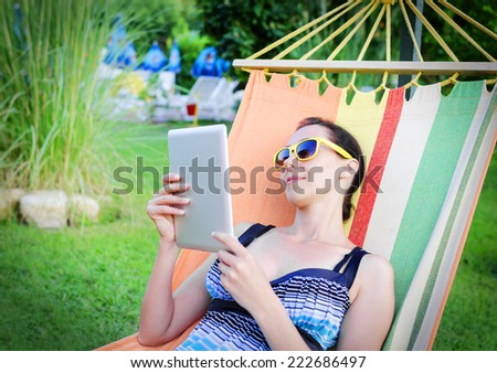 Woman Relaxing In Hammock With Tablet PC - stock photo