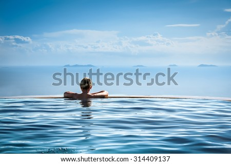 Woman relaxing in infinity swimming pool looking at view - stock photo