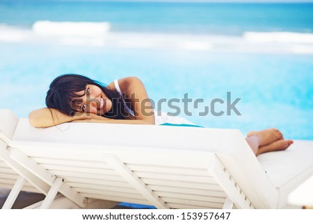 woman relaxing in resort on a sunbed - stock photo