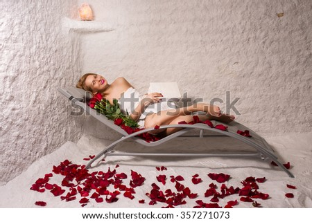 woman relaxing in salt room with book, roses and petals - stock photo