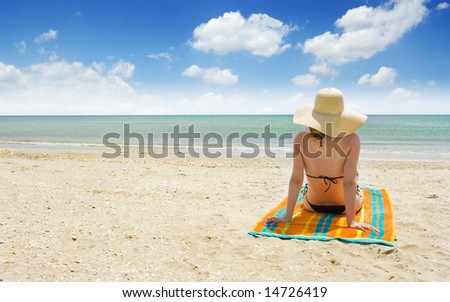woman relaxing on a beautiful beach against sunny sky - stock photo