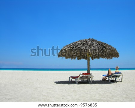 woman relaxing on a lounger reading a book at a tropical beach - stock photo